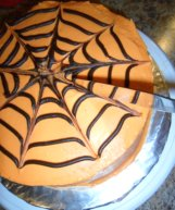 Using a knife to drag the icing on the Spider Web Cake